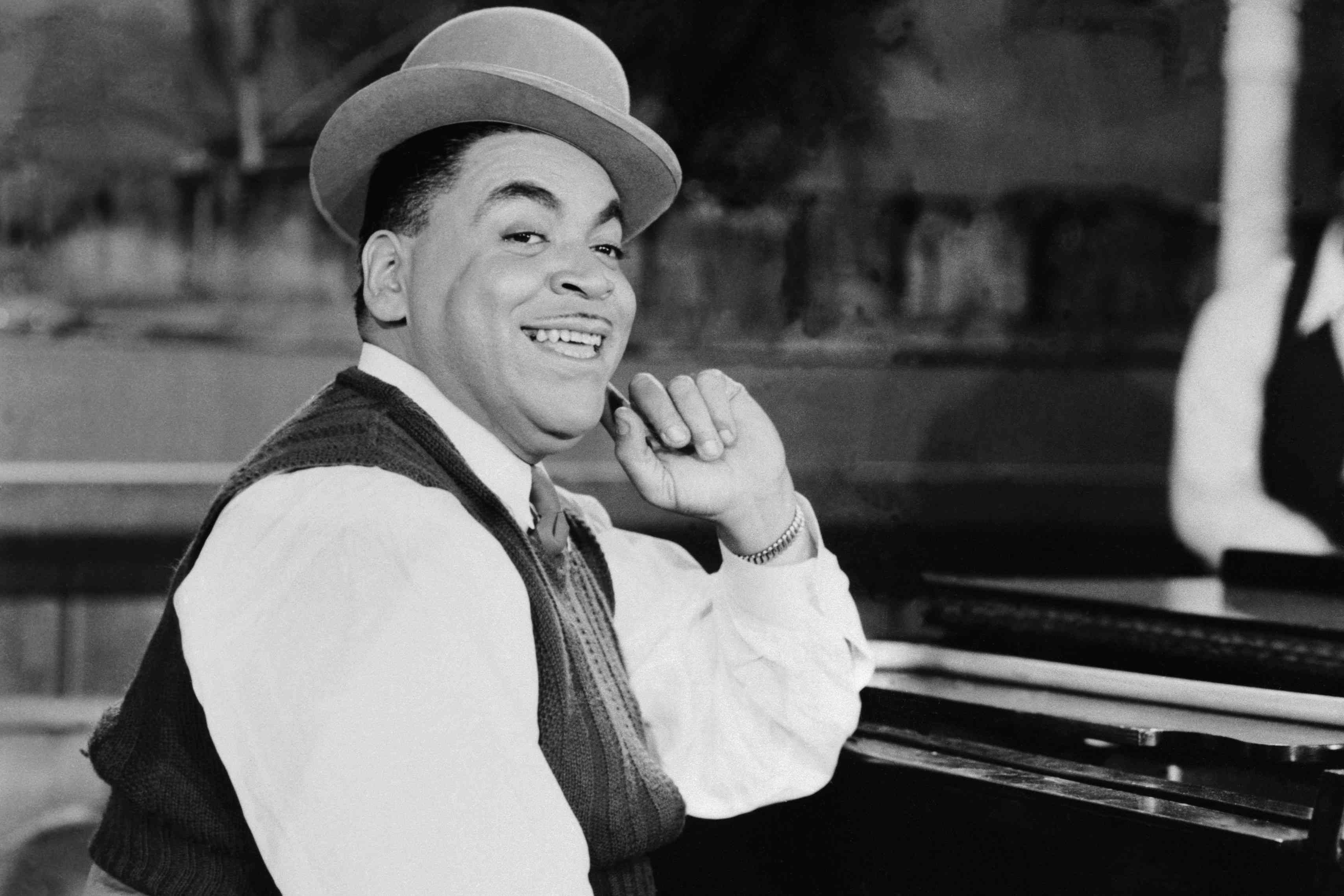 Fats Waller leaning against a piano and smiling, wearing a hat and vest