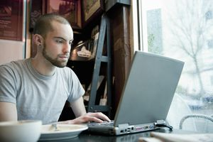 Young man using laptop in coffee shop