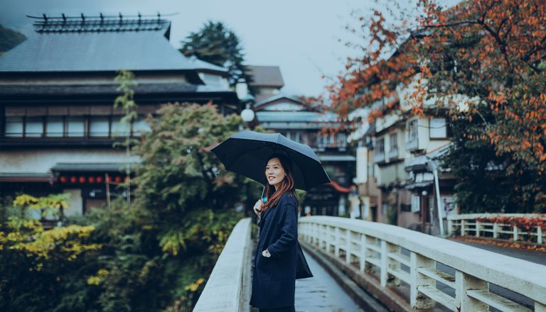 Pretty young lady walking along the old town and enjoying the scenics in a Japanese Zen Garden on a rainy day.