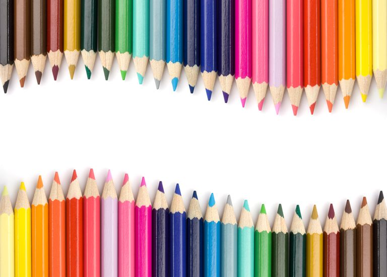 Top view of colored pencils frame arranged on white background.