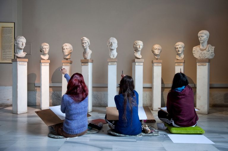 Students examining ancient sculptures.