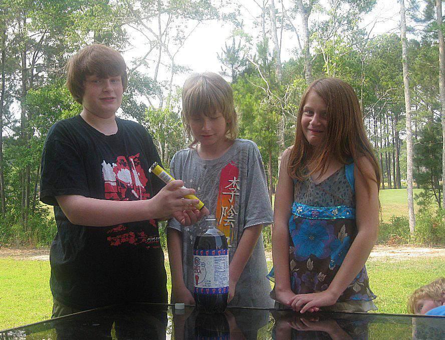 Children putting mentos into soda