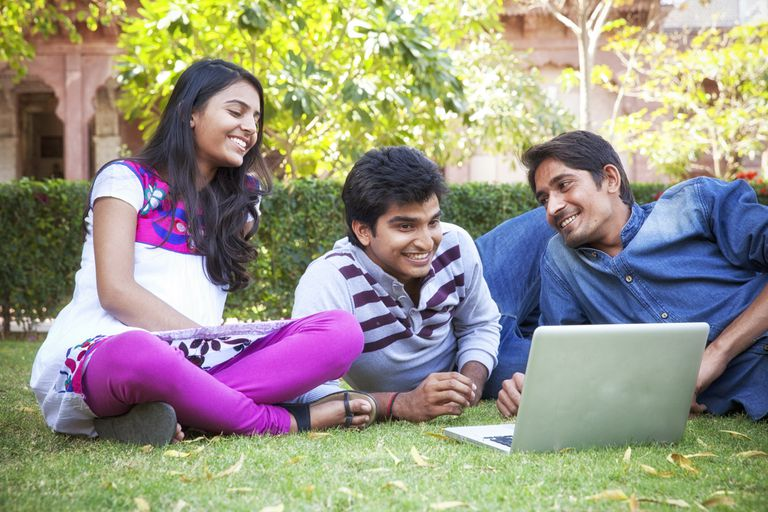 three students on the grass looking at a laptop