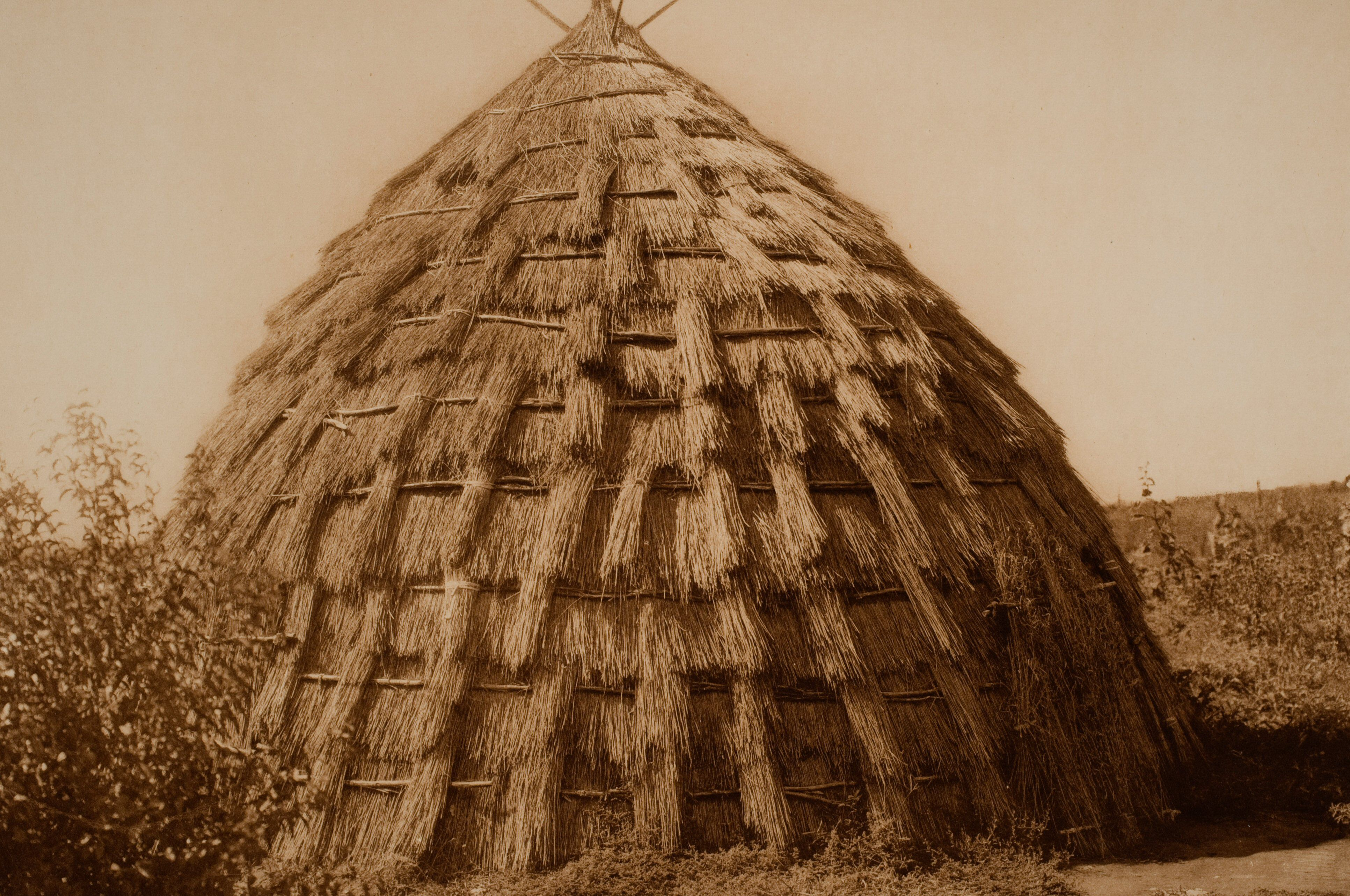 historic sepia photo of a domed hut made of grass