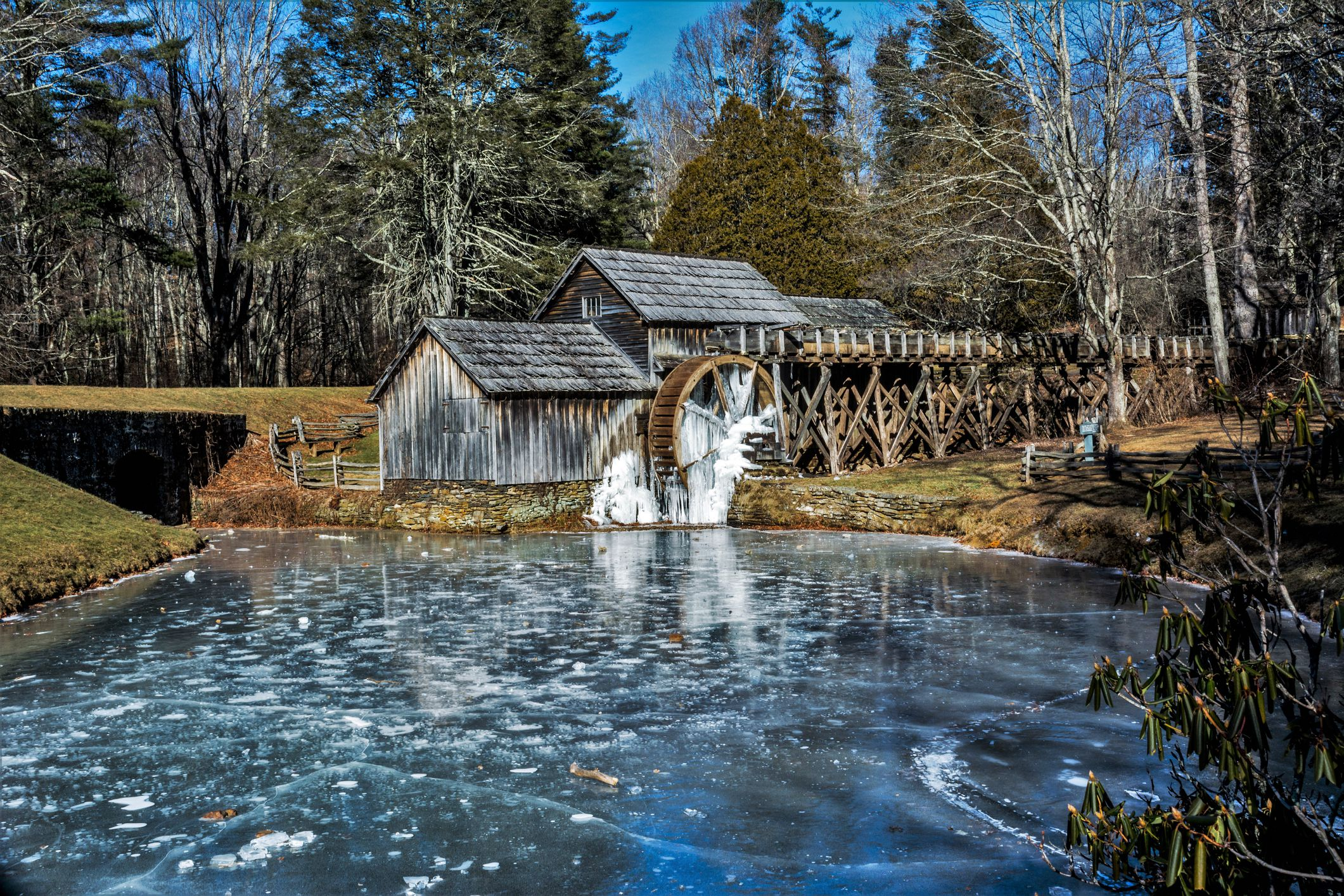 Mill with a water wheel built on a river surrounded by trees.