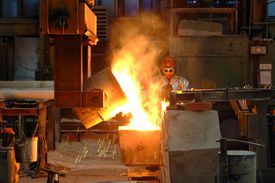 A laborer in safety gear oversees as one cauldron full of melted metal is poured into another