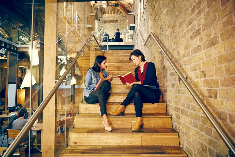 2 woman sitting on a staircase reading a book