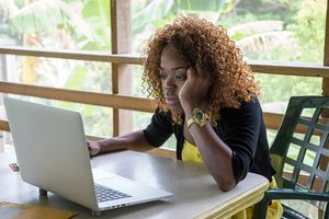 woman looking at laptop next to windows in office.