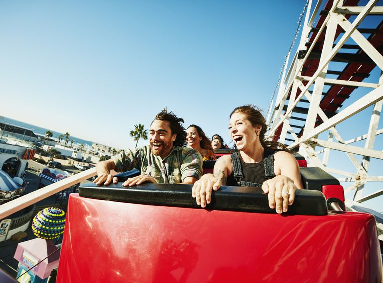 People on a roller coaster laugh and smile.
