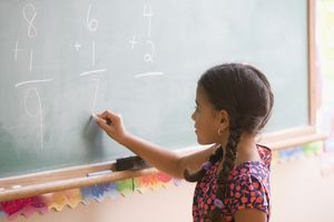 girl doing math on blackboard