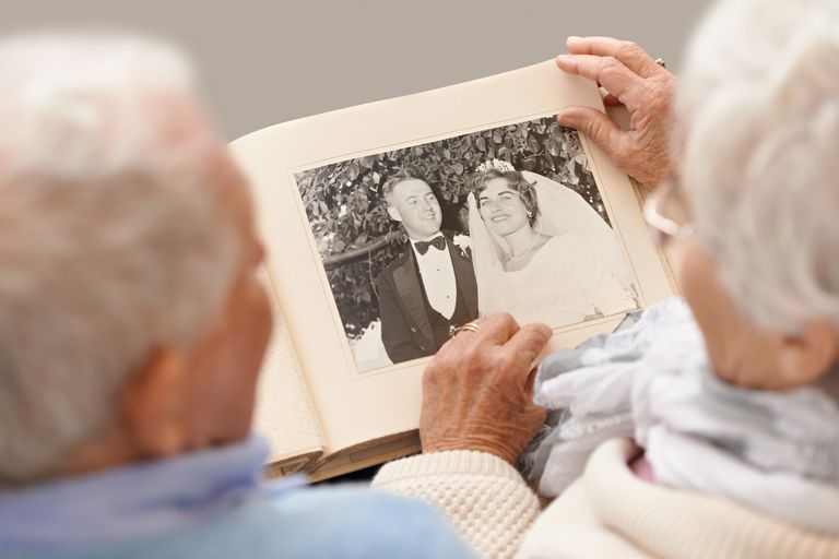 Older couple looking at an photo of themselves in their youth.