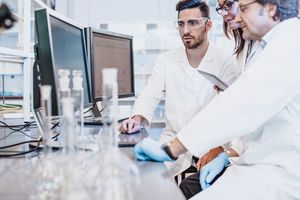Scientists using computer together in the lab