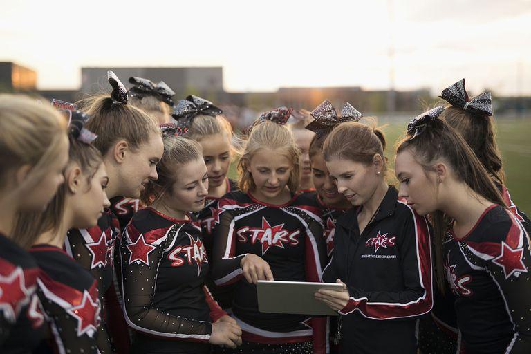 High School Cheerleading Team Using Digital Tablet
