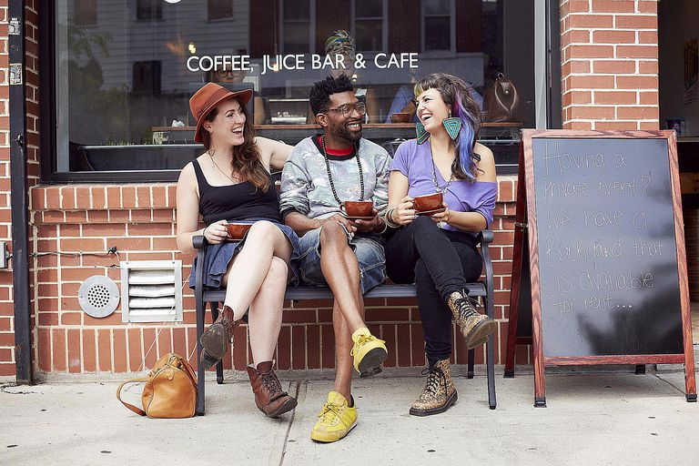 A group of young people laughing outside a cafe