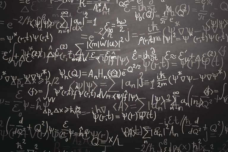A chalkboard covered in complex mathematical equations