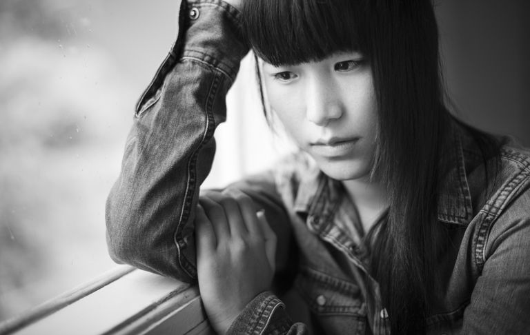Asian teenager girl sitting near window with sadness.