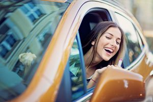 woman looking in car mirror to put on lipstick