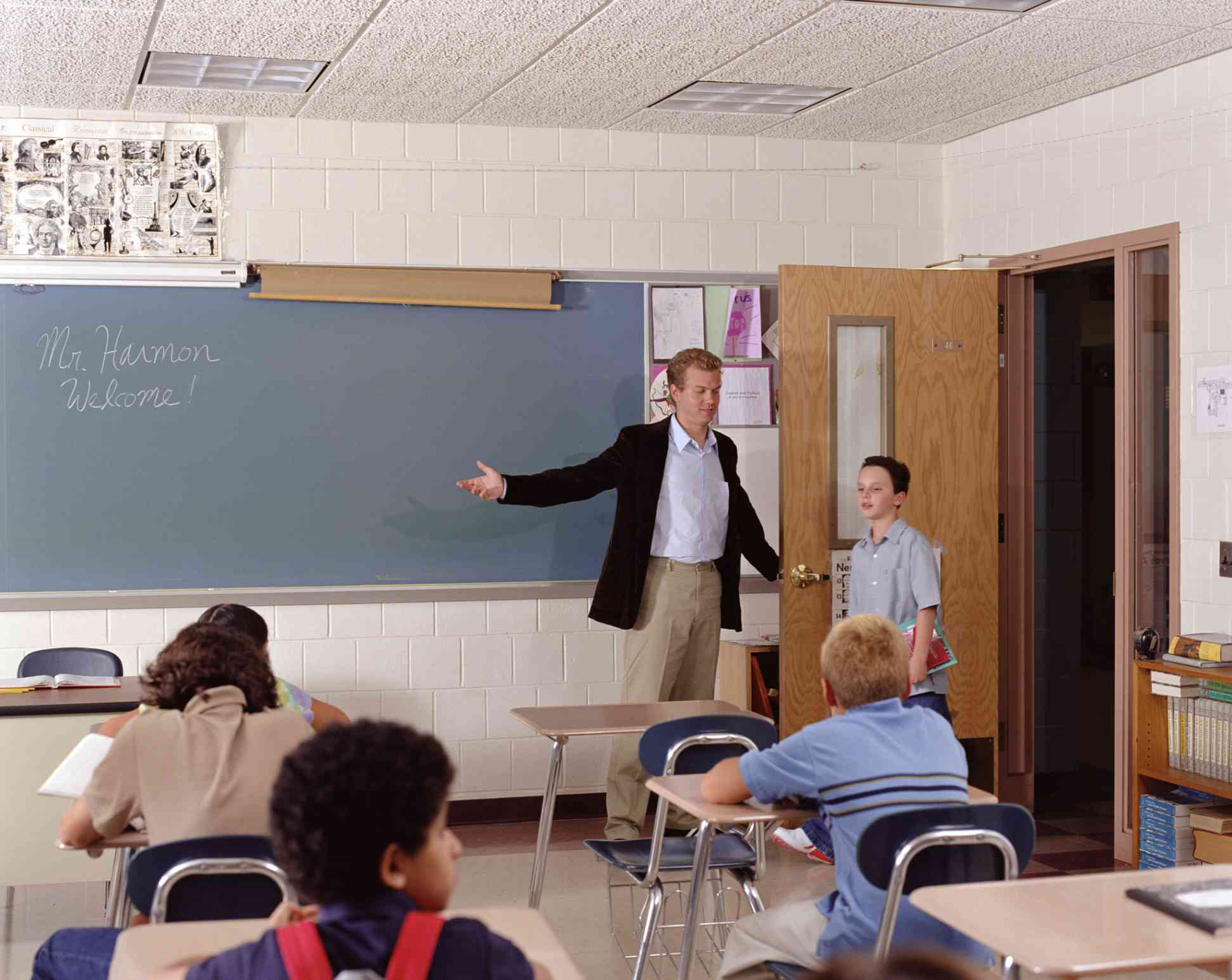teacher letting a student into classroom