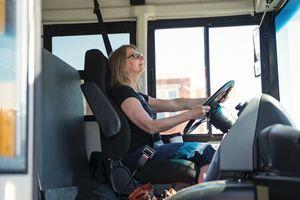 Portrait of mature woman driving a school bus.