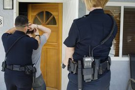A police officer arrests a man in front of a door to a house.