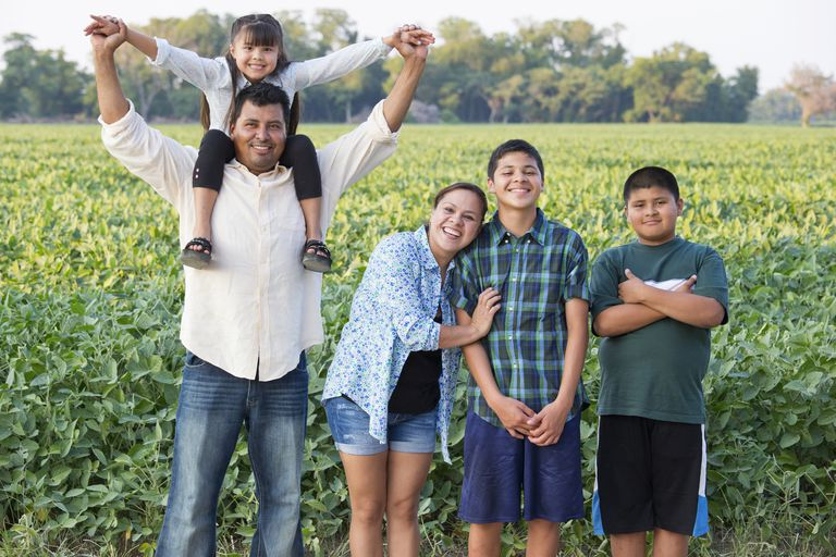 Hispanic family smiling in crop field