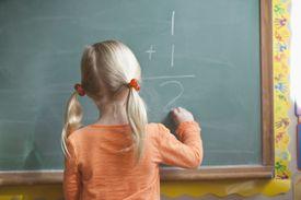 Girl solving math problem on blackboard
