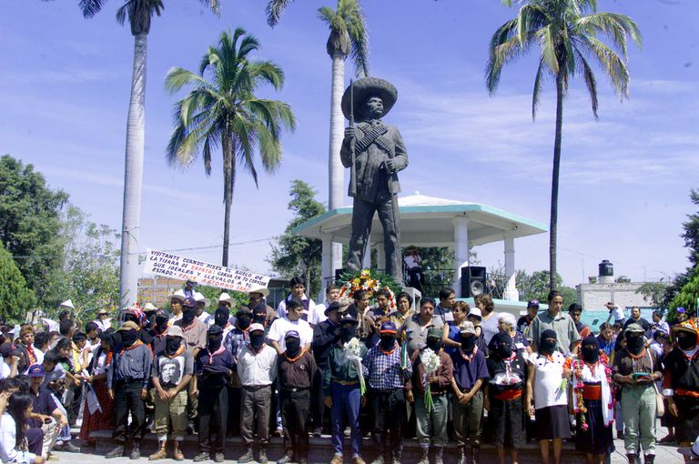The EZLN stands in front of a statue of Emiliano Zapata