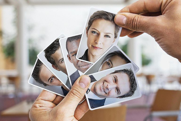 A person selects images of people from a pile, signaling the concept of sampling design in sociology