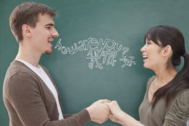 Two people conversing in front of a chalkboard with writing in two different languages