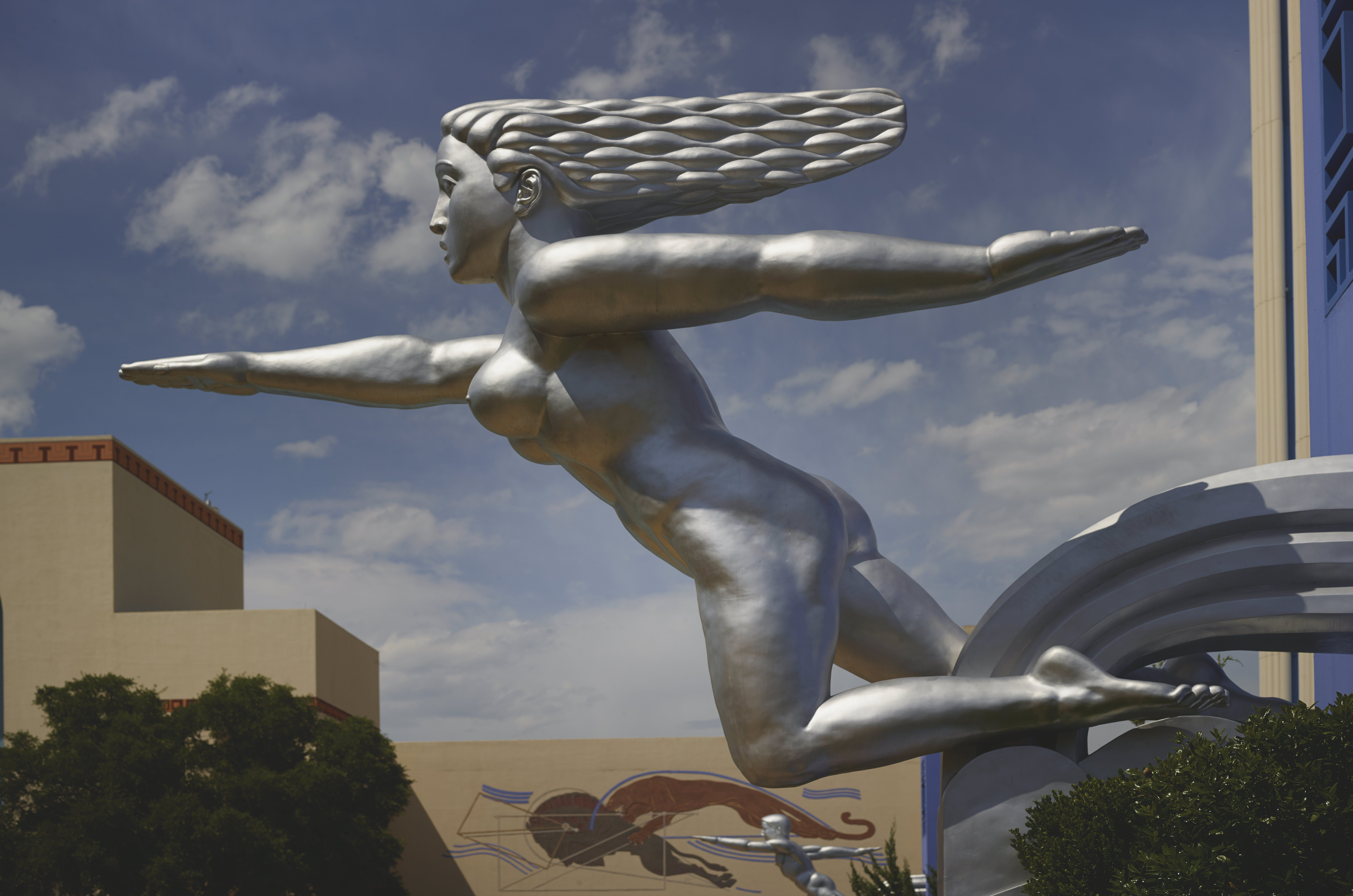 silver sculpture of naked woman seemingly running, hair flowing behind, one arm forward and one arm behind