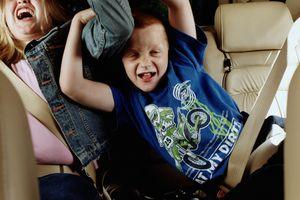 Siblings (8-12) fighting in backseat of car