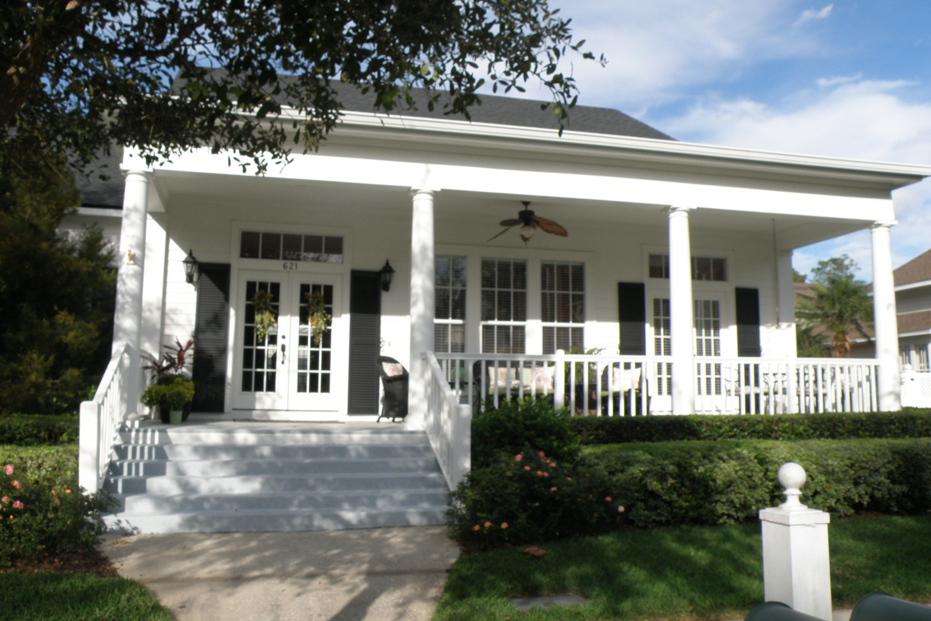 lefthand entrance to bungalow with two front doors, low roof, and front porch the width of the front