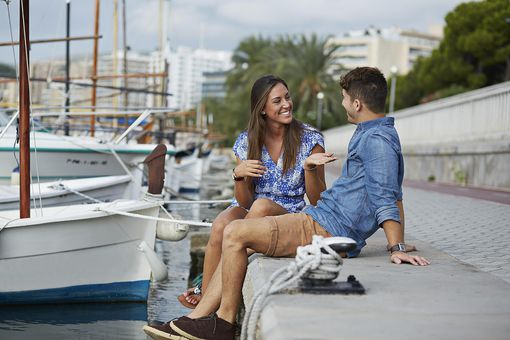 Young couple hanging out at small harbor