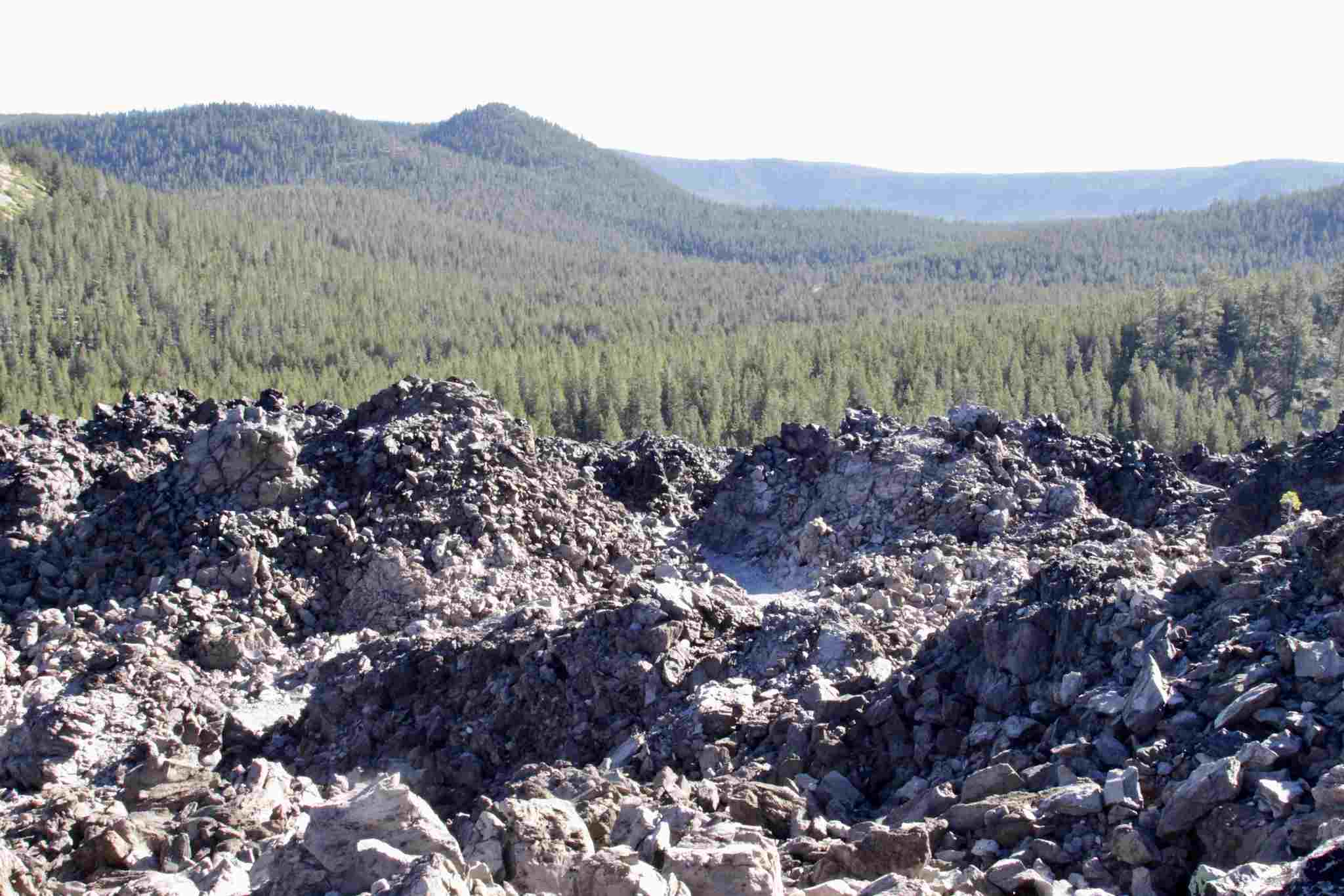 Large obsidian flow on a bright, sunny day, with rolling hills in the background.