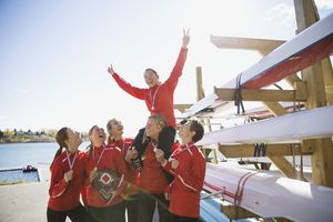 Rowing team with medals celebrating near sculls