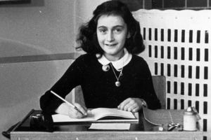 Black and white photo of Anne Frank writing in a notebook while sitting at a desk.