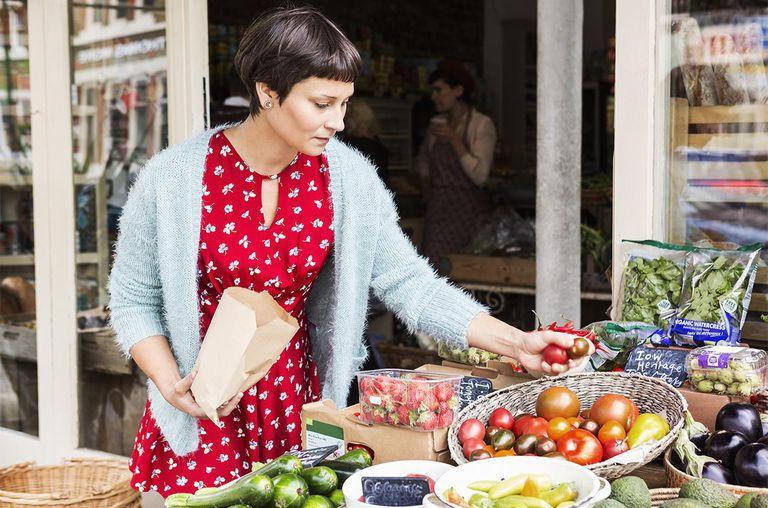 Woman selecting tomatoes at local farm shop.