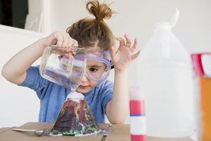 young girl pouring liquid into volcano model
