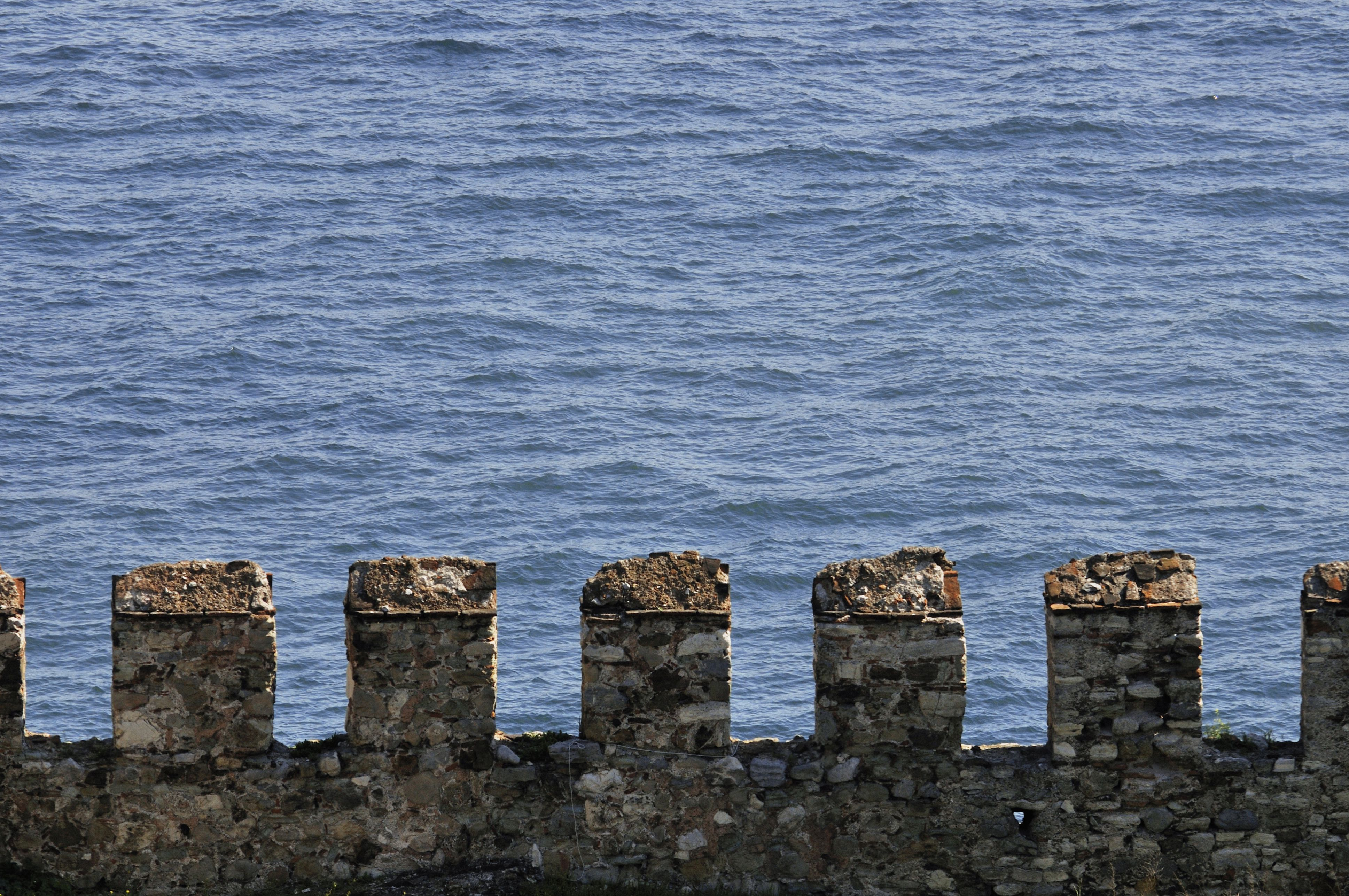 stone projections rising from a stone wall overlooking water