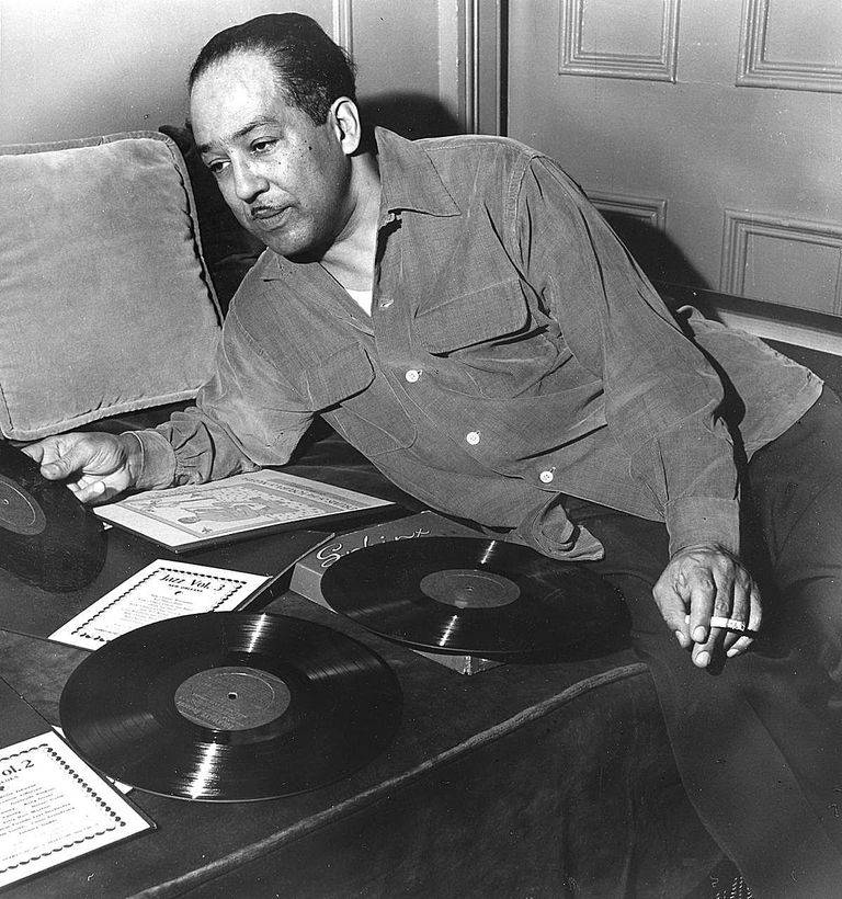 Langston Hughes leaning over records on a couch.