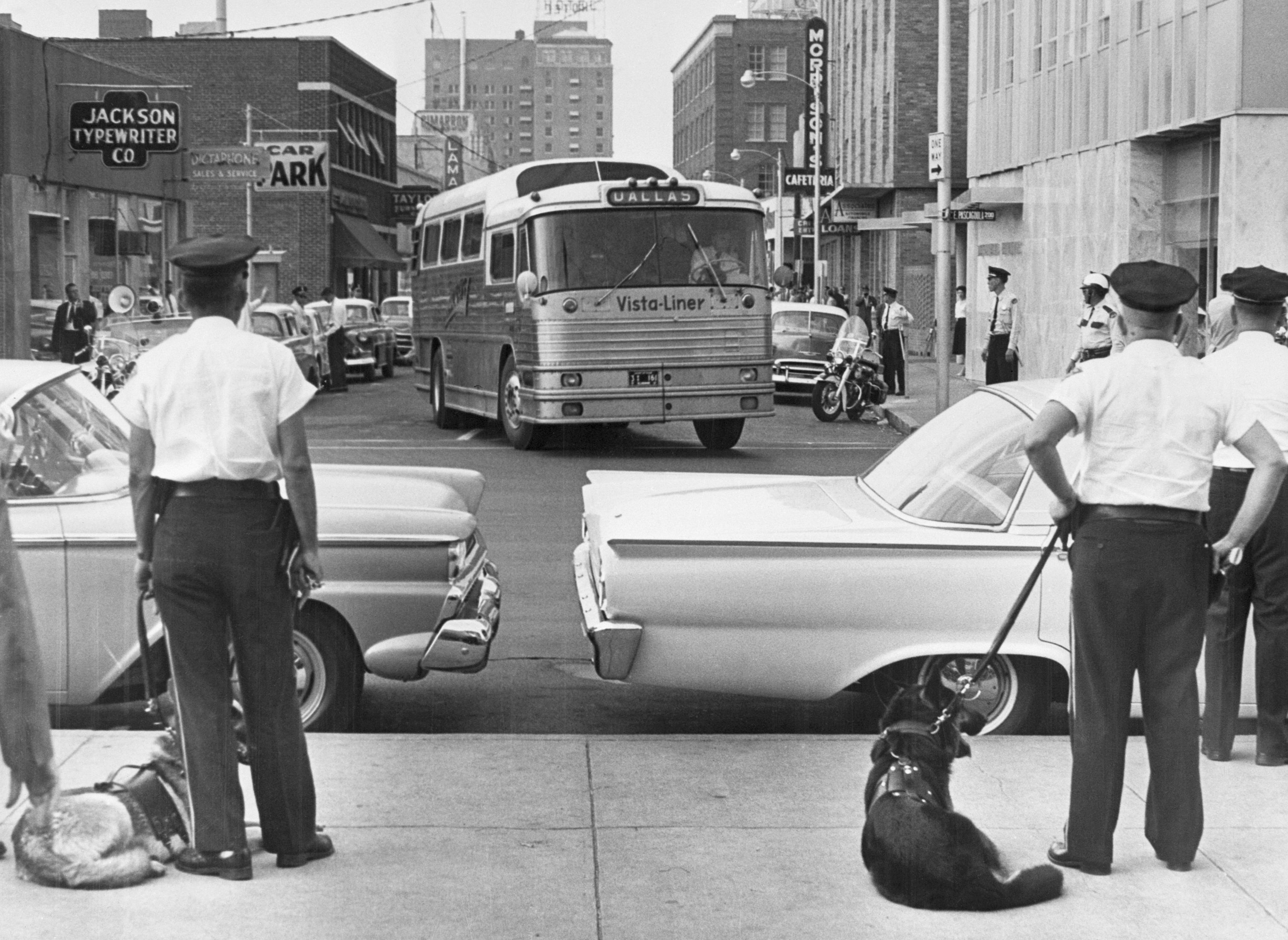 Freedom Riders Arriving in Jackson, Mississippi to a group of policemen and their dogs.