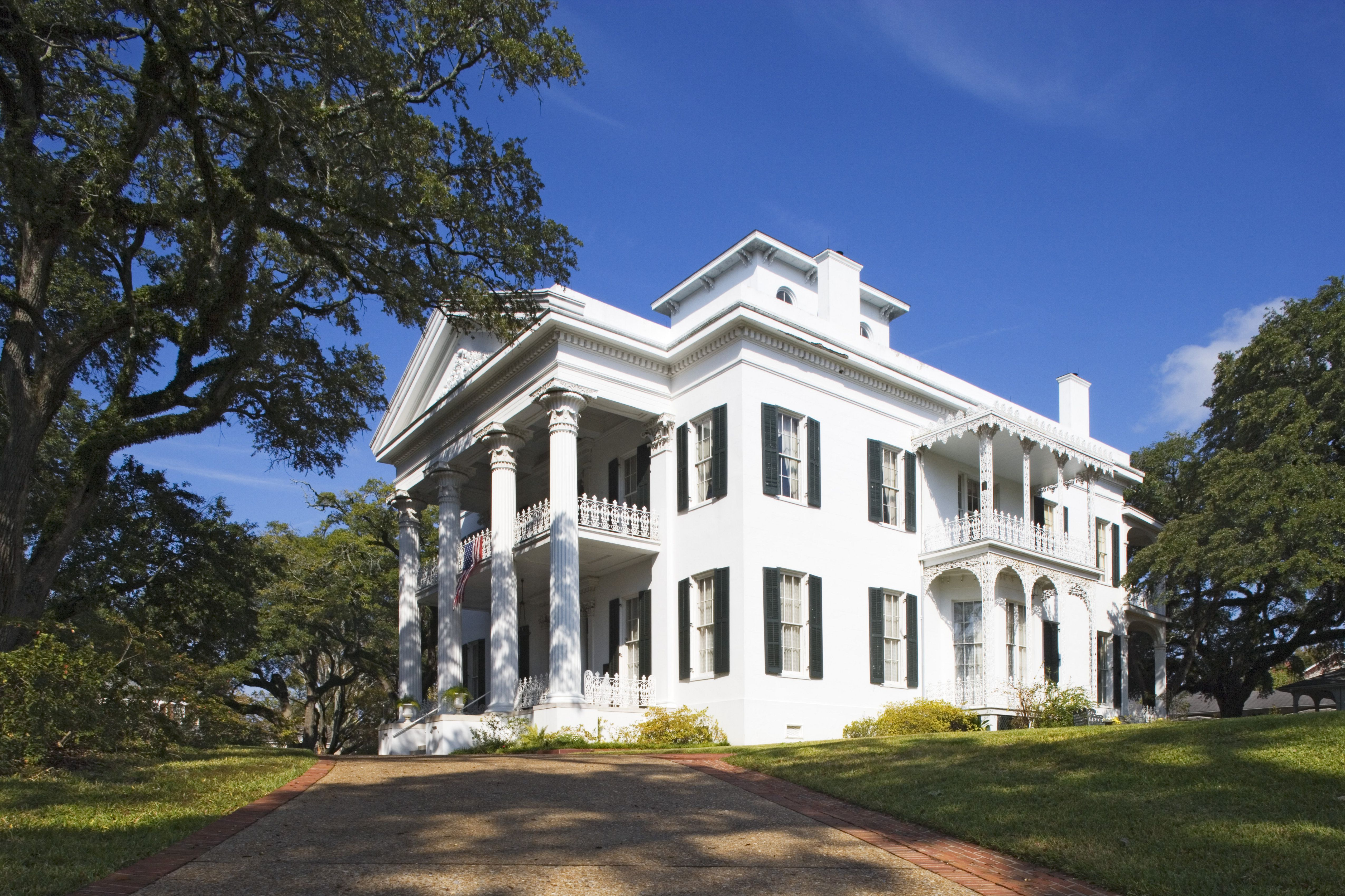 Large white antebellum plantation house, pillars holding up pediment and two porches