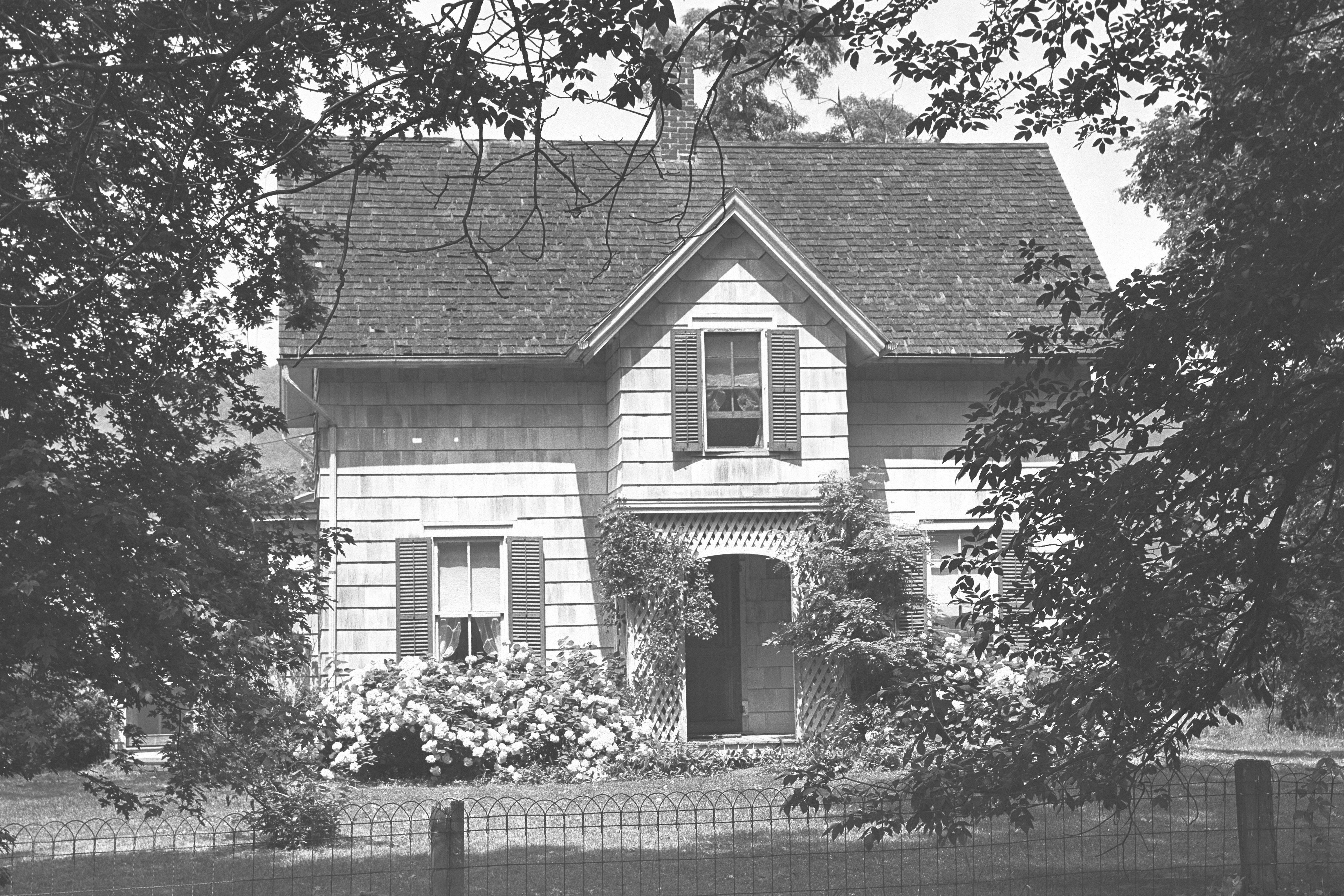 Vintage black and white photo of a two-story cottage and fence
