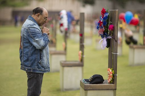 Man prays at memorial chair before the memorial service as Oklahoma City marks the 21st anniversary of the terrorist bombing on April 19, 2016 in Oklahoma City, Oklahoma.