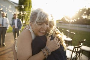 Affectionate senior bride hugging friend in sunny rural garden
