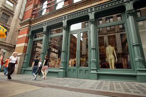 Street-level cast-iron facade painted green, engaged columns with capitals define large glass display windows