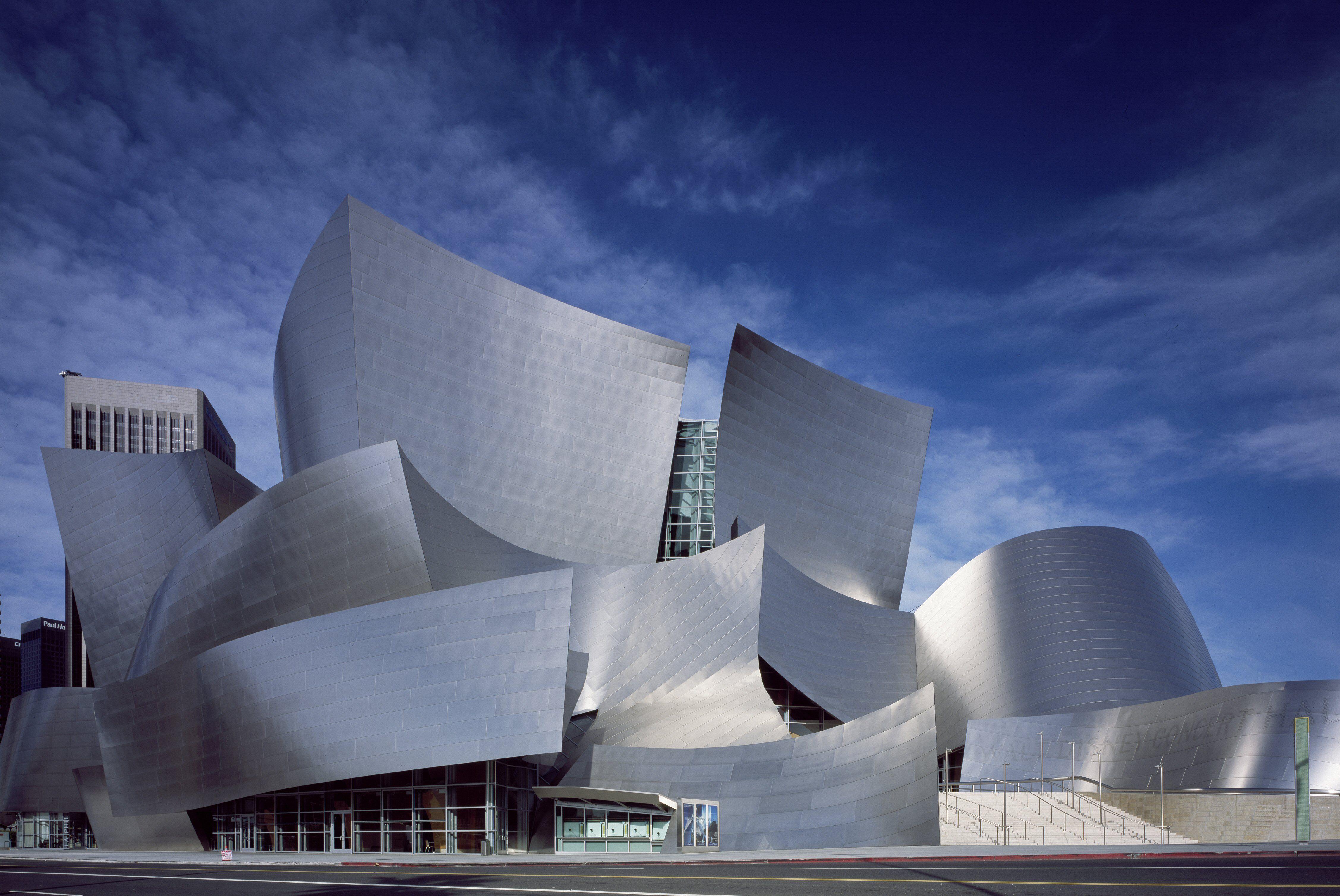 shiny, gray, curvy modern building with panes of glass peeking