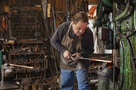 Blacksmith using a power hammer to shape hot steel in his workshop