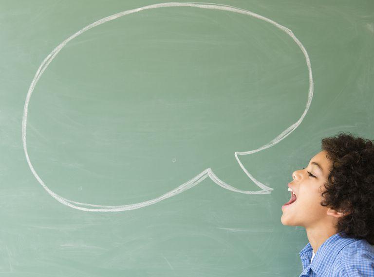 Mixed race boy shouting into speech bubble on chalkboard