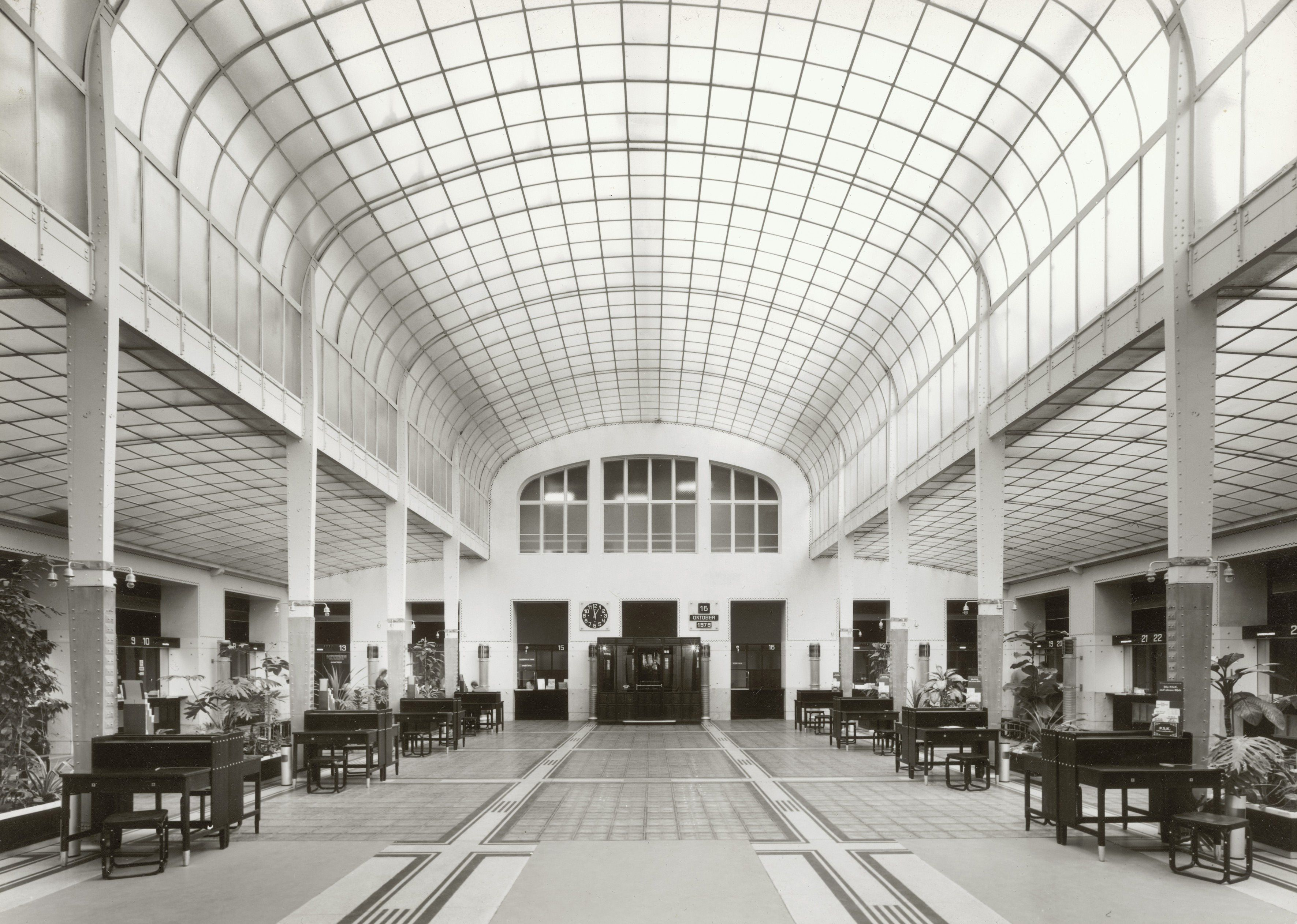 historic black and white photo of large interior, longer than wide, curved light ceiling, teller desks along each wall